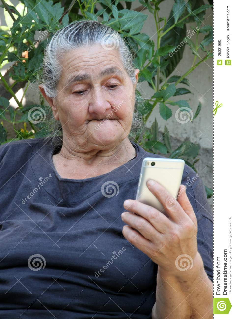 Old woman looking on a smartphone