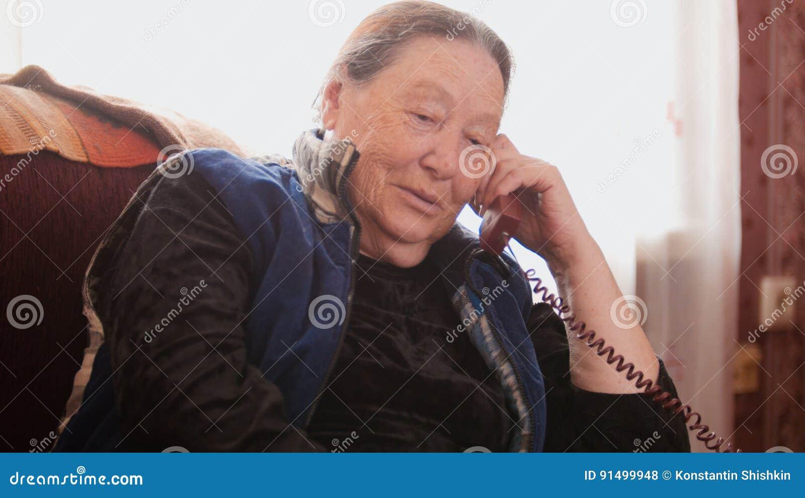 Old Woman pensioner speak landline telephone and smiling, close up