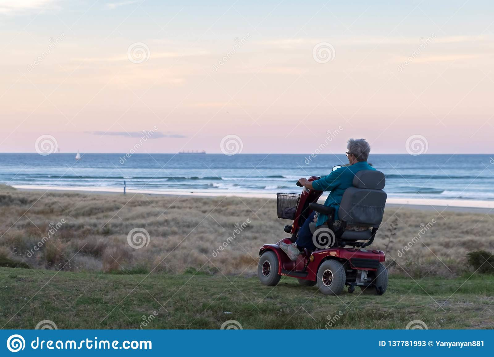 An old woman rides on a electric powered wheelchair parked on the beach at sunset time, in a lonely atmosphere. Lonely widow old