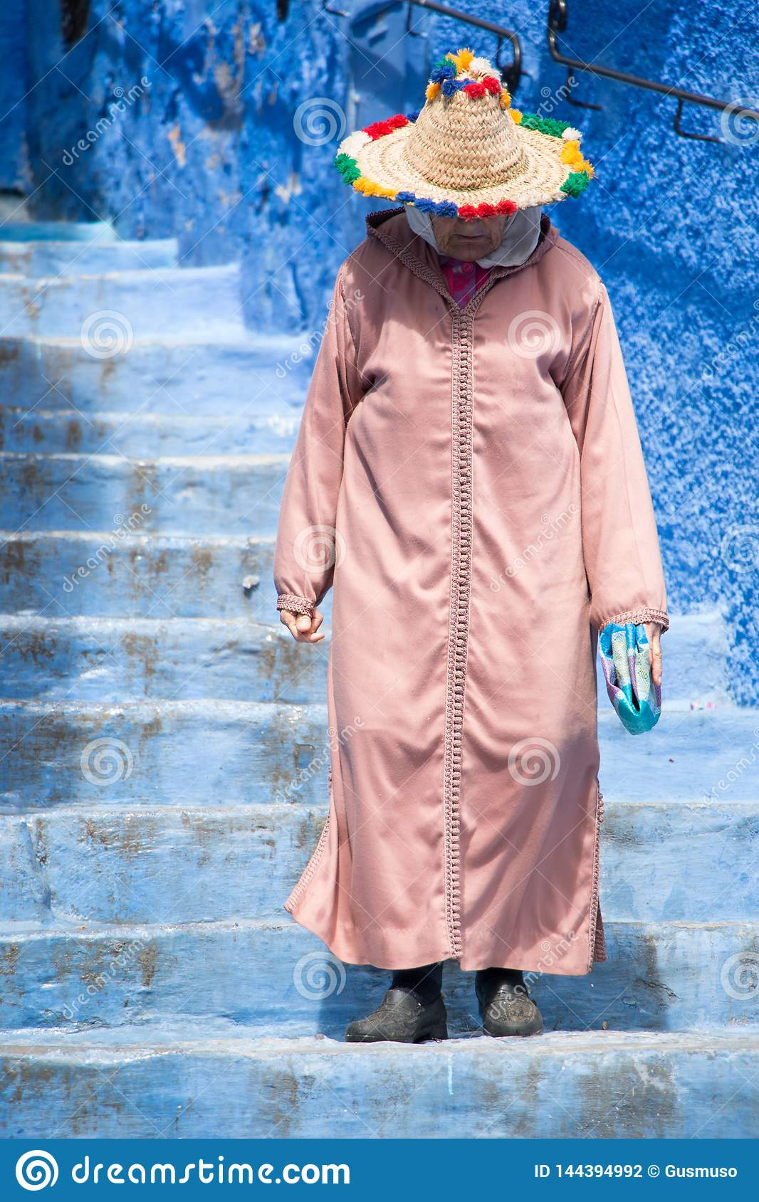 An old woman strolls through the streets of Chefchaouen, the blue town in Morocco, with her traditional costume
