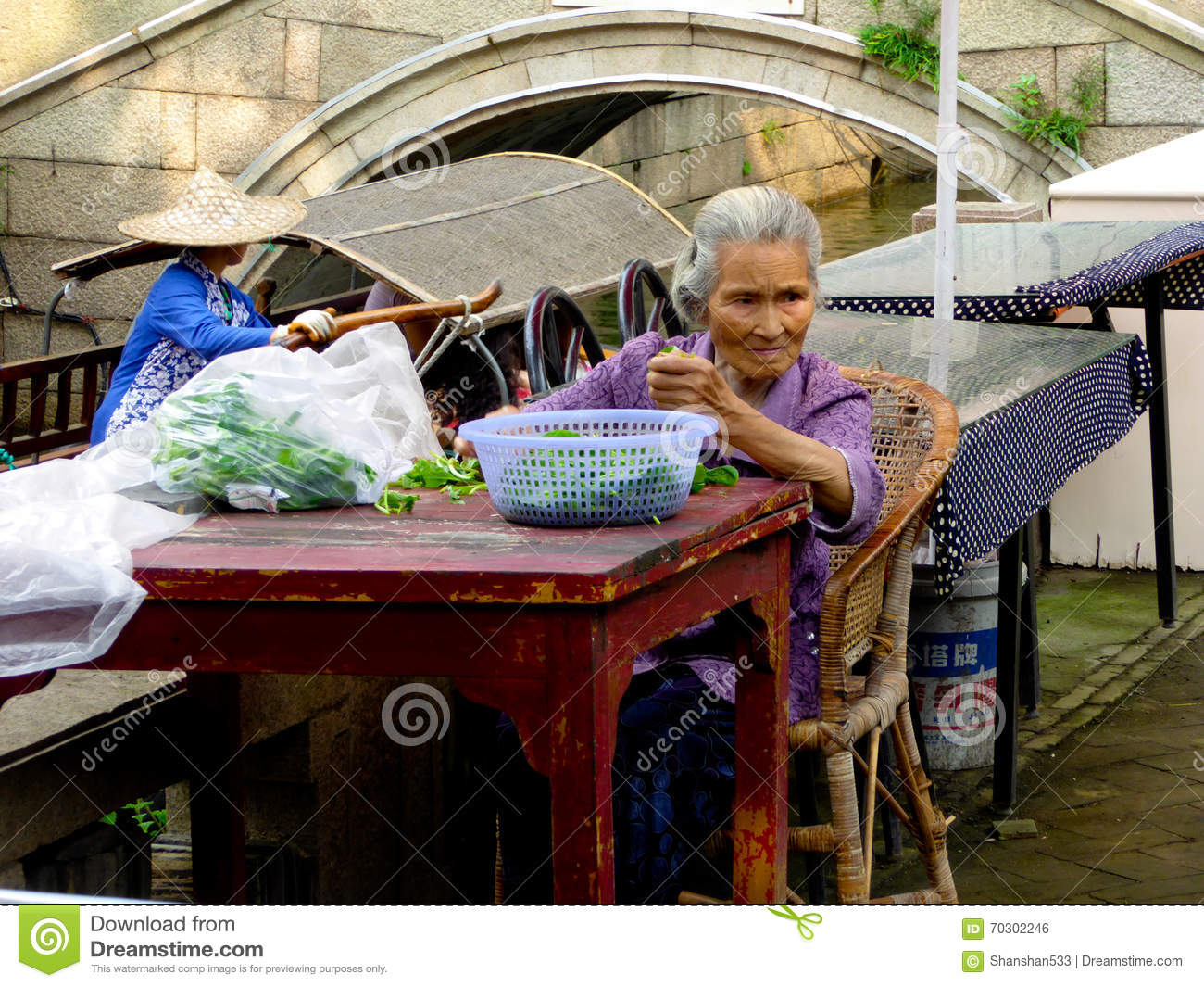 Old woman triming vegetables for cooking
