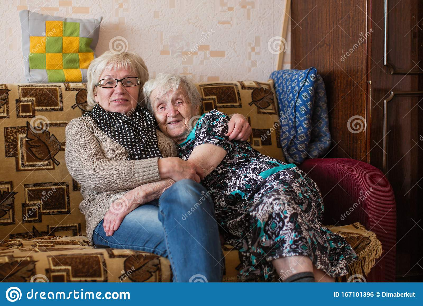 Old Woman With Her Adult Daughter Cuddling On The Couch Family