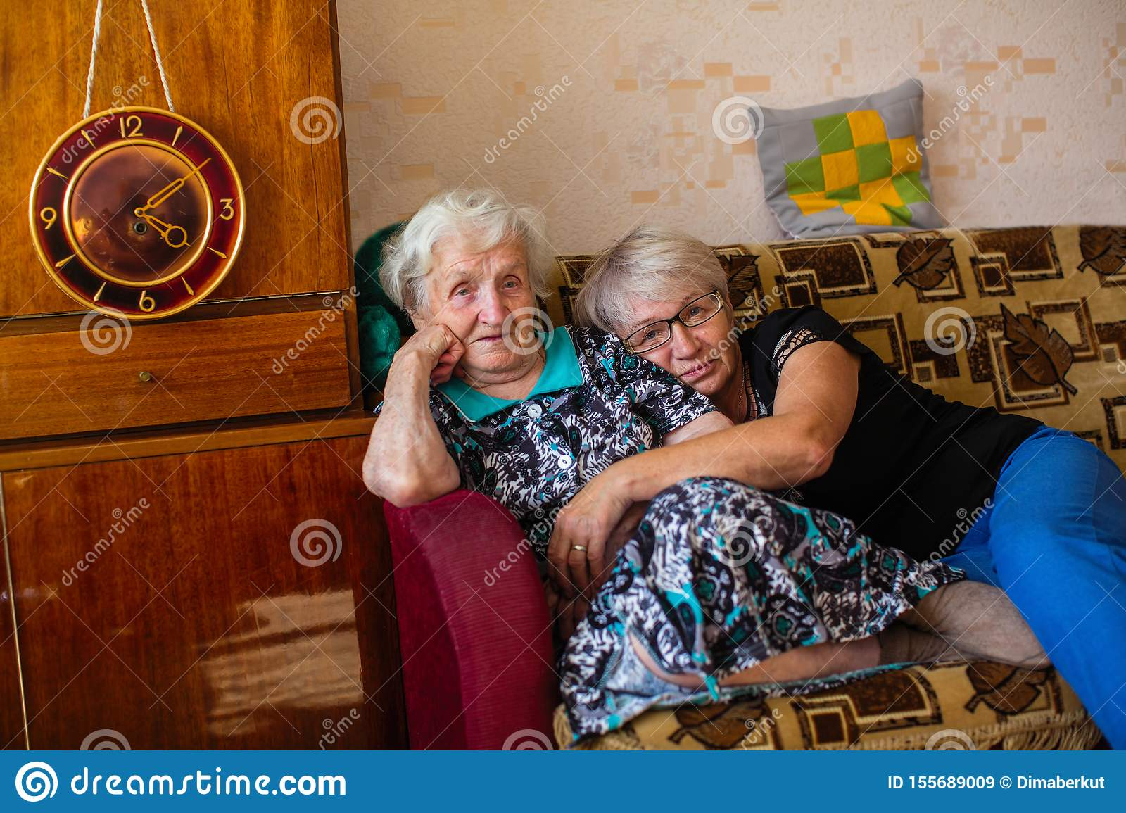 Old Woman With Her Adult Daughter Sitting On The Couch Love