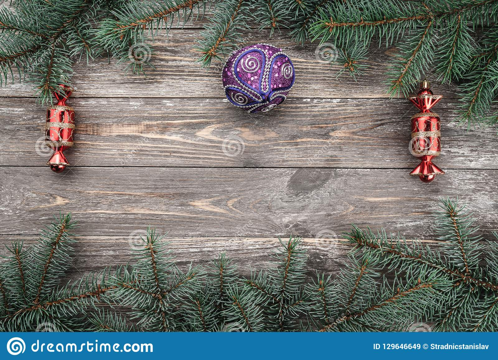 Old wood background with fir branches with toys. Space for a greeting message. Christmas card. Top view