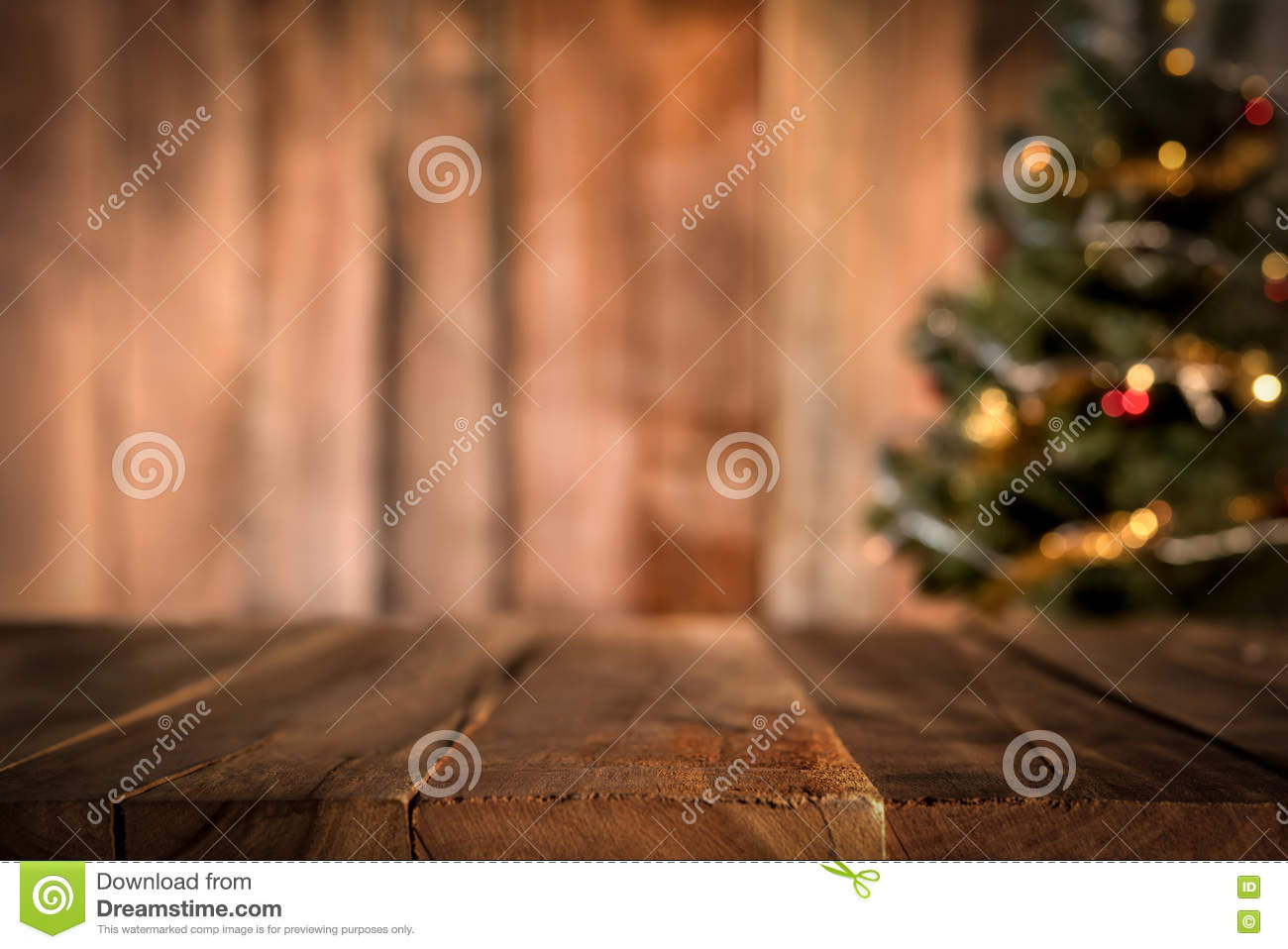 Old wood table top with blur Christmas tree in background