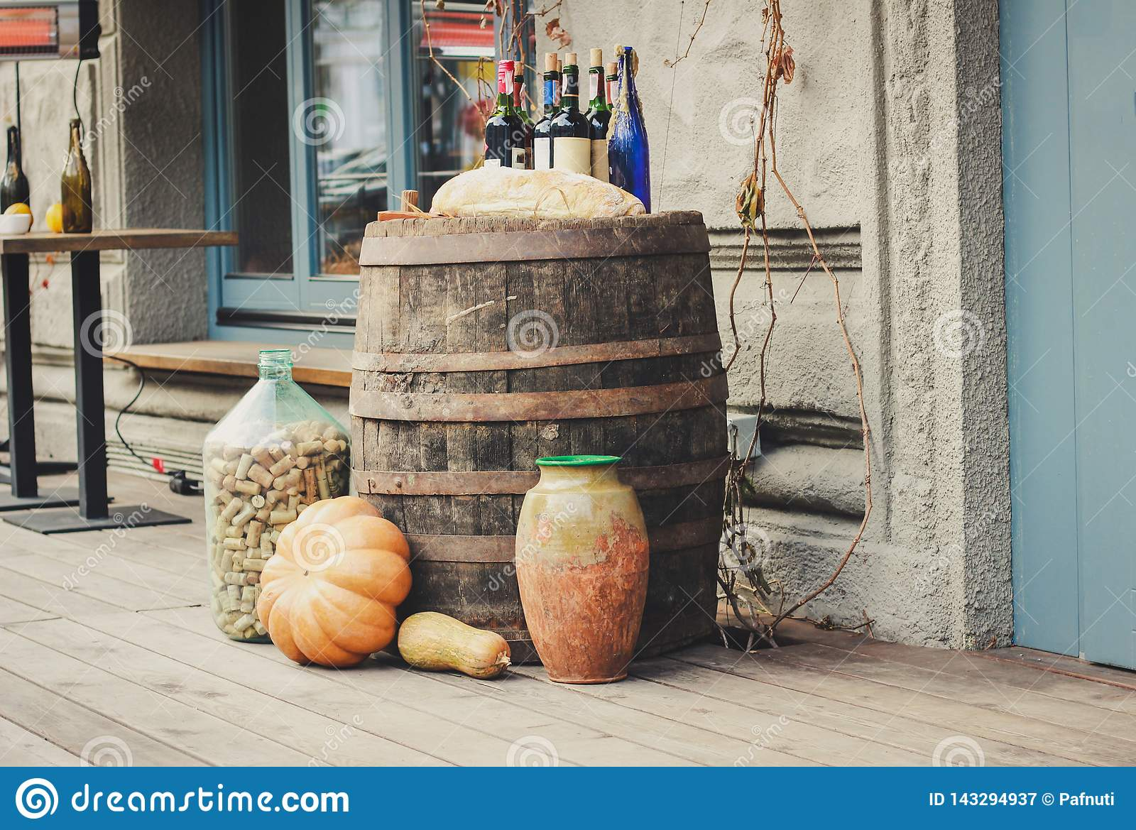 Old wooden barrels on which there are pumpkins and bottles.