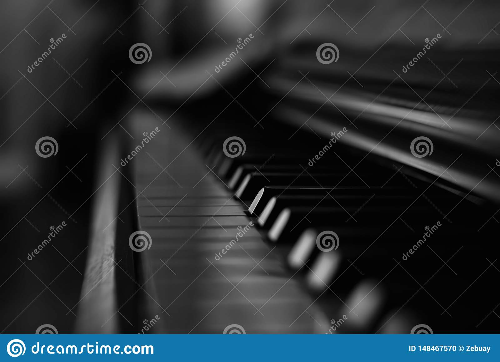 Old and wooden black and white piano keyboard in darknes with music