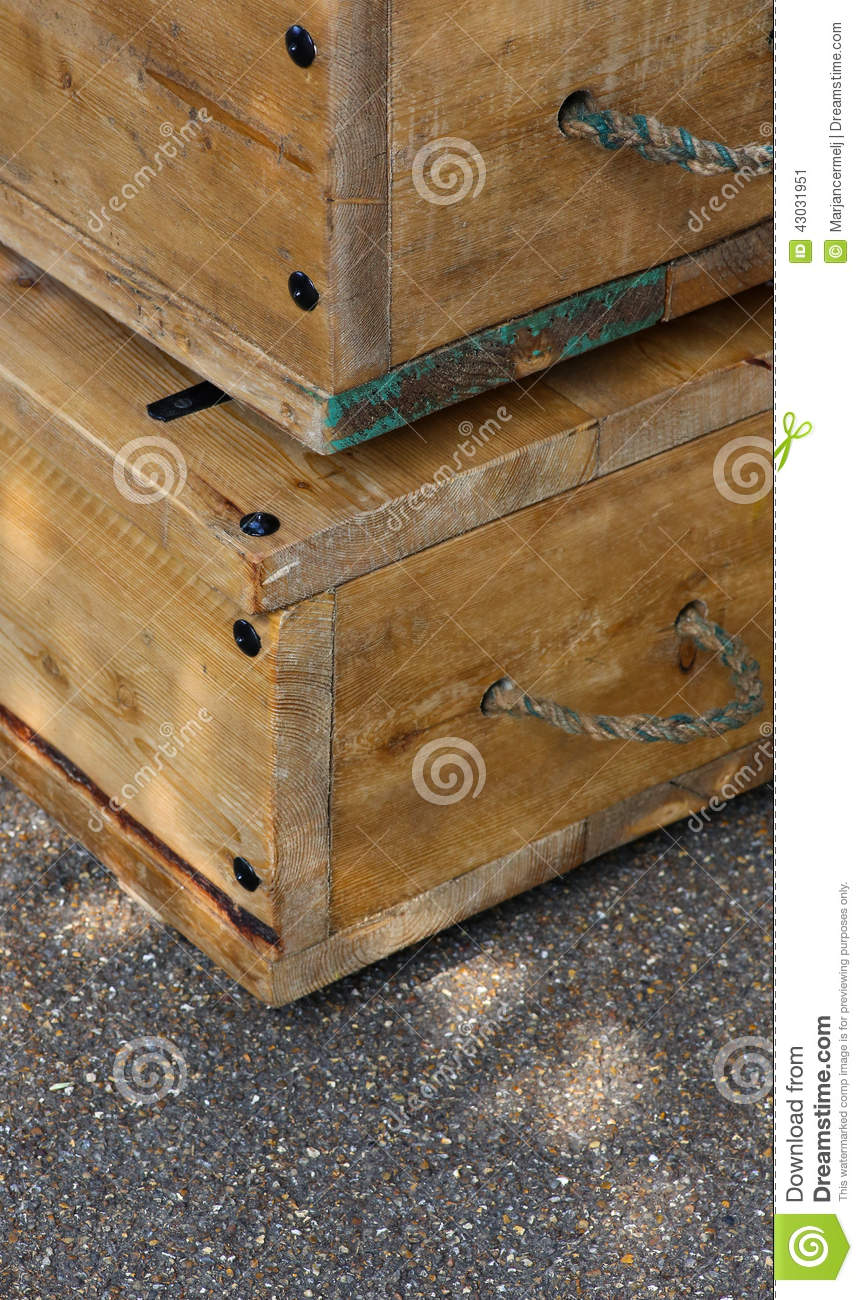 Old wooden boxes with rope handles on street stock image