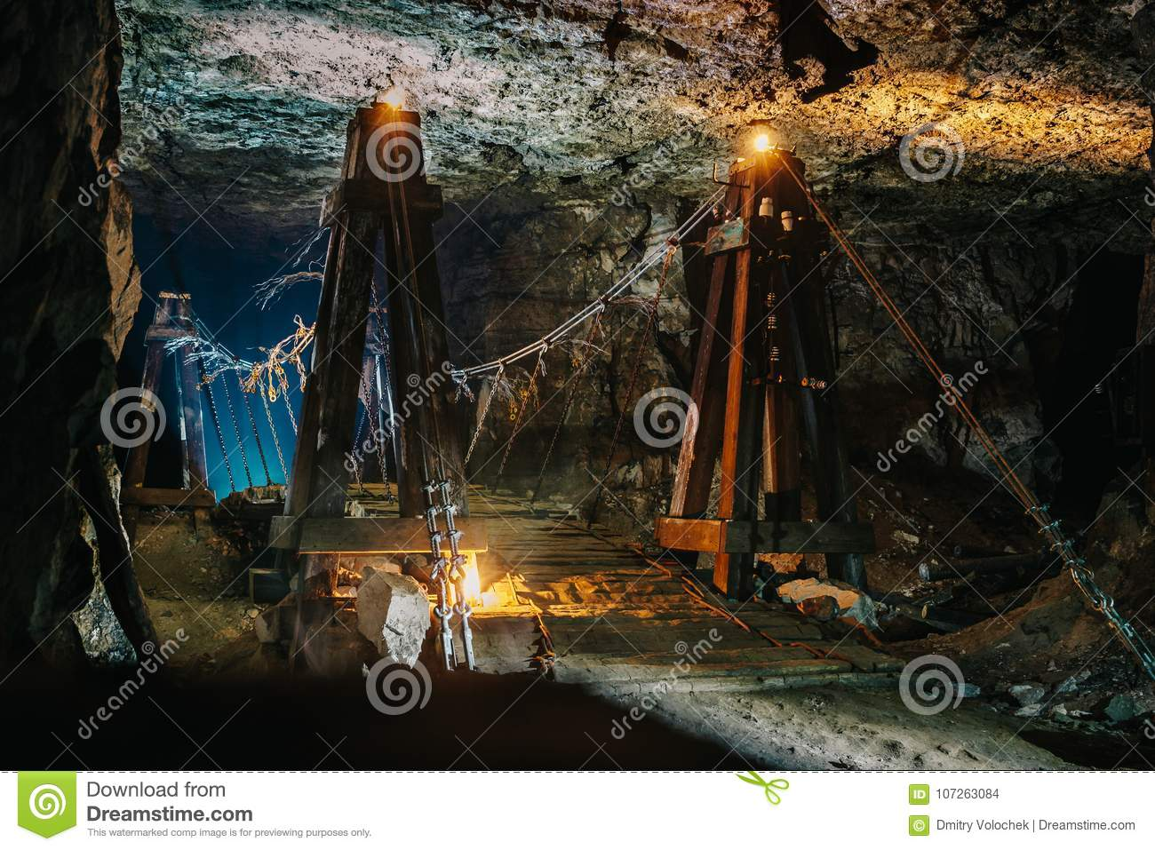 Old wooden bridge in scary abandoned underground limestone mine cave or tunnel or dark corridor with mysterious illumination