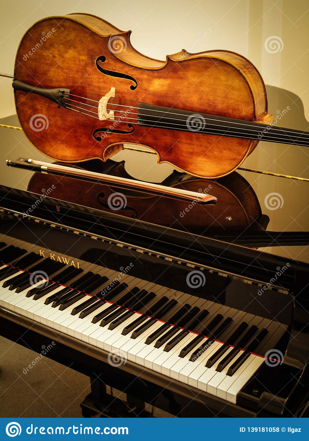 Old wooden Cello and bow on grand piano with cream background