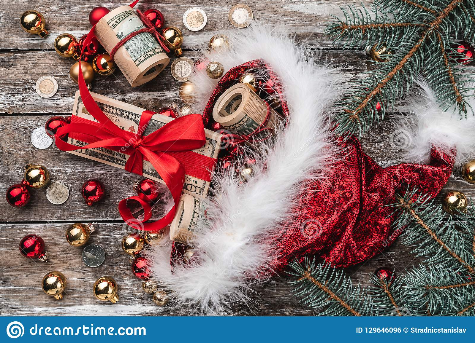 Old wooden Christmas background, Santa Claus, baubles and money coins and Xmas items. Top view