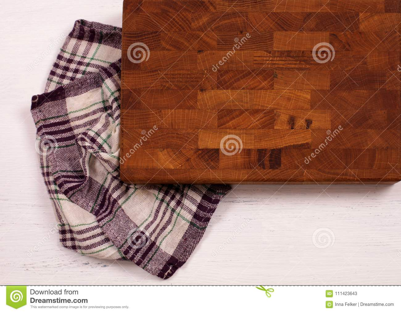 Old wooden cutting board with kitchen towel on white wooden table.