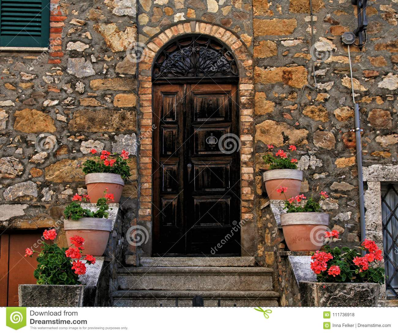 Old wooden door decorated with flowerpots and steps in medieval