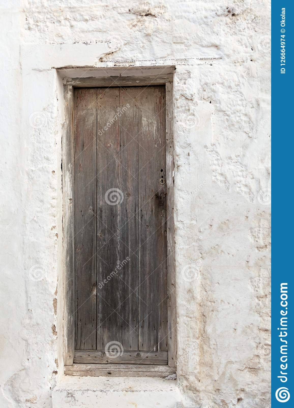 Old wooden door on grunge weathered wall.