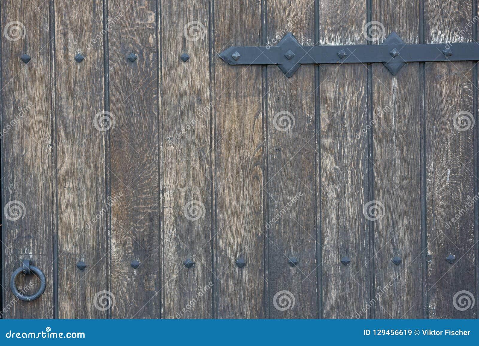 Old wooden door in the stone wall from medieval era. Vintage metal padlock on a wooden door.