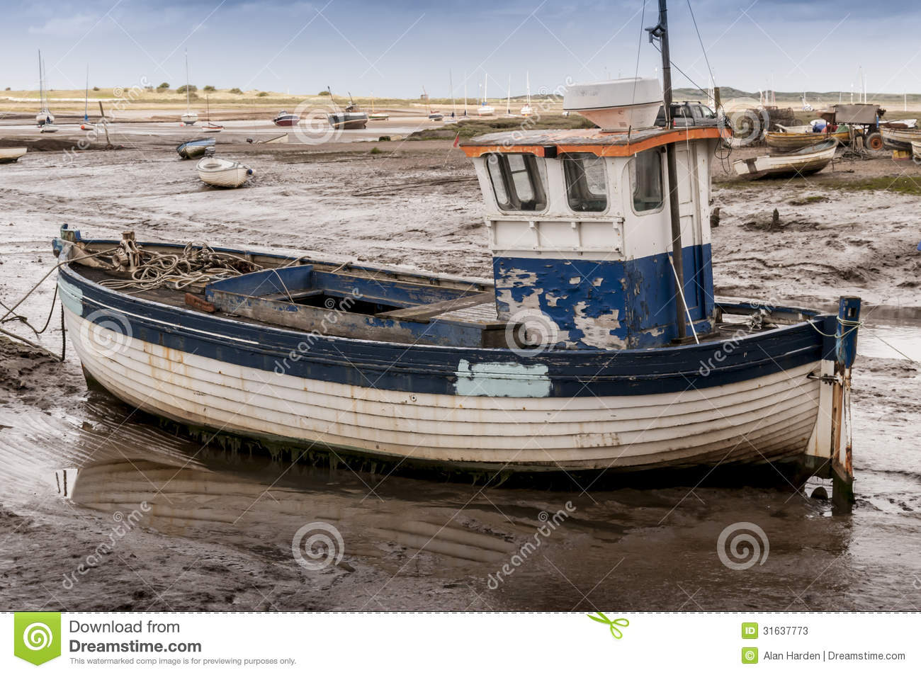 Old wooden fishing boat on mud flats at Brancaster Norfolk England.