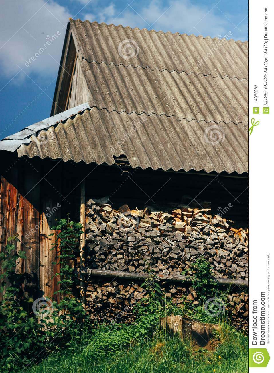 Old wooden house with fire wood on top of hill mountains in sun