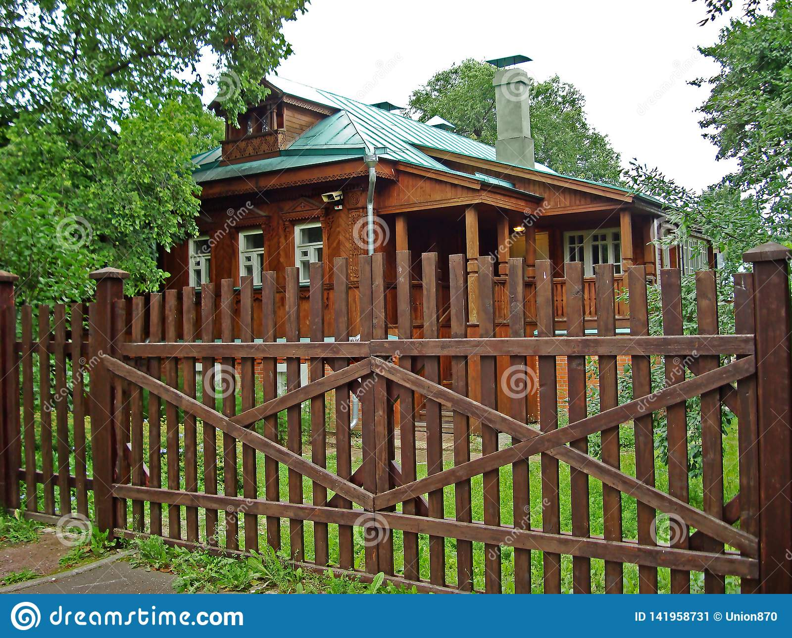 Old wooden house with green roof and brown fence