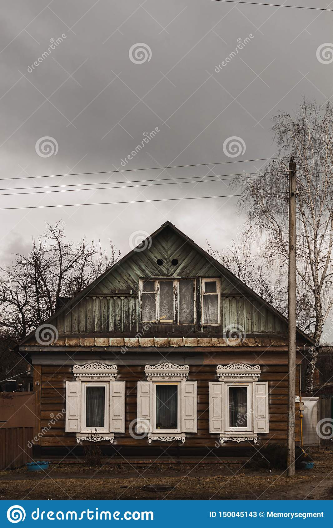 Old wooden house with white shutters in cloudy weather
