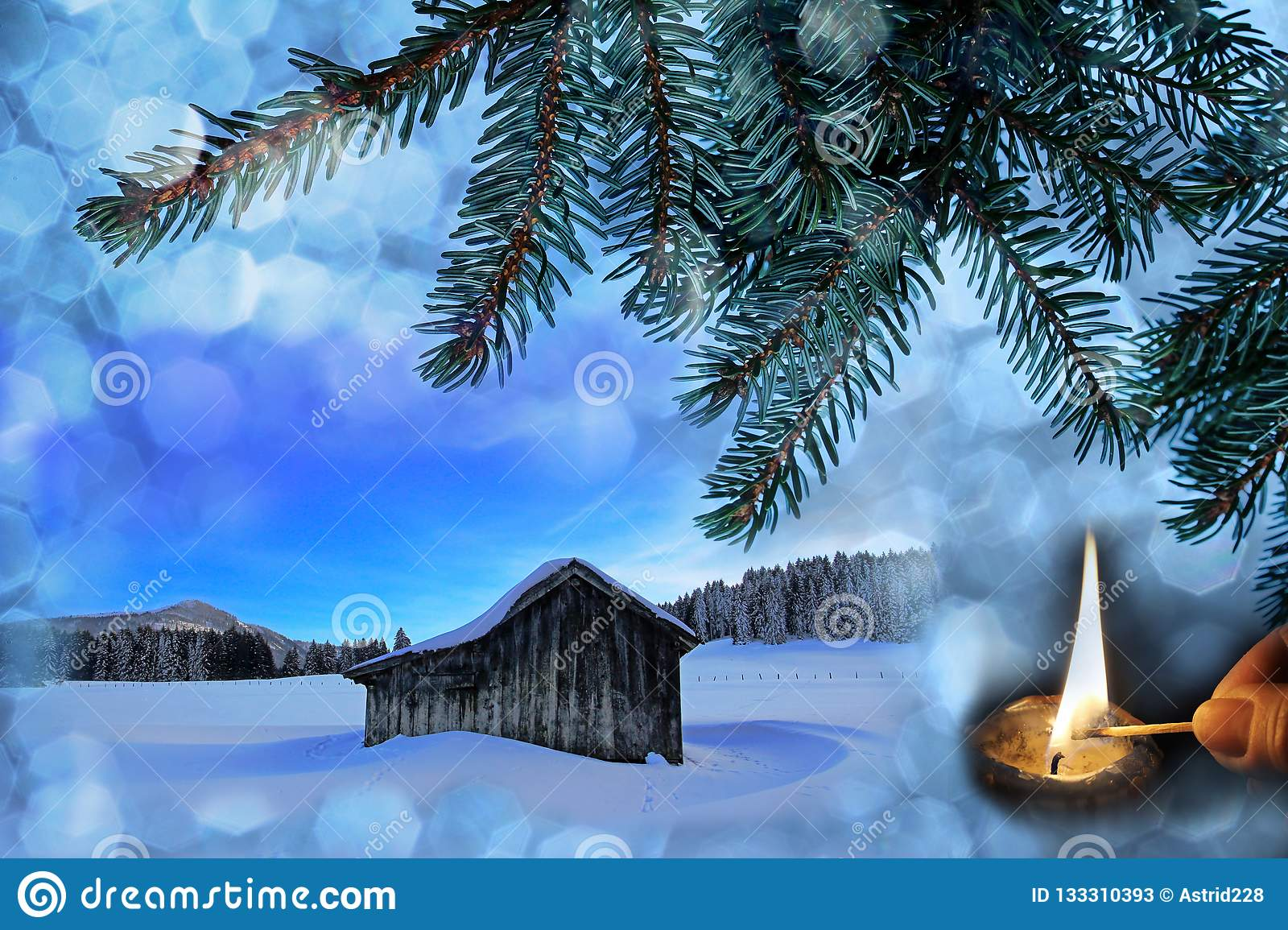An old wooden hut in the snow with Christmas snowflakes, fir branches and a burning candle