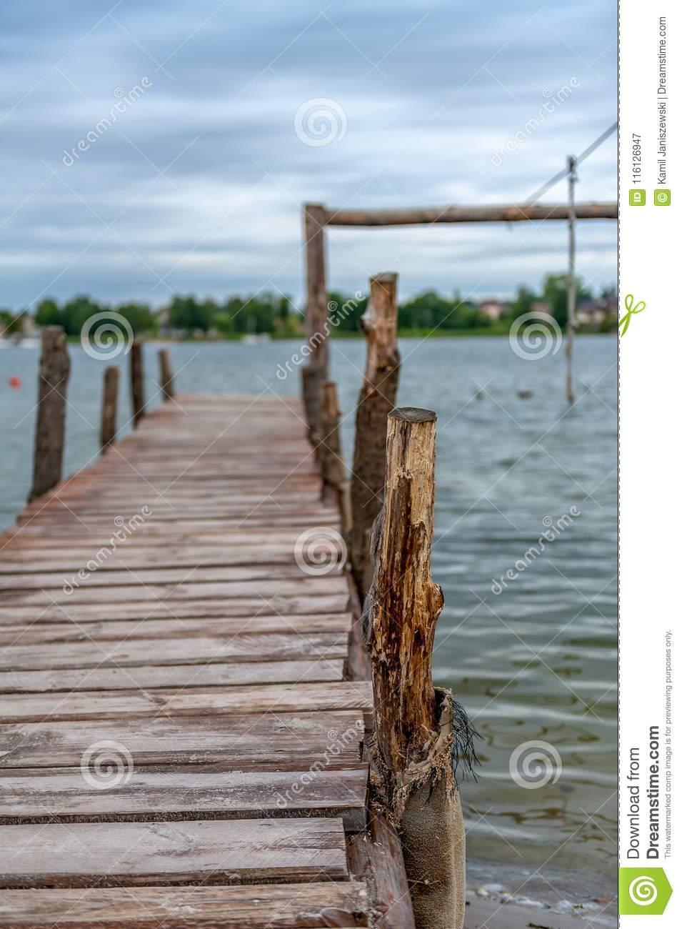 Old wooden pier with a lake in the background