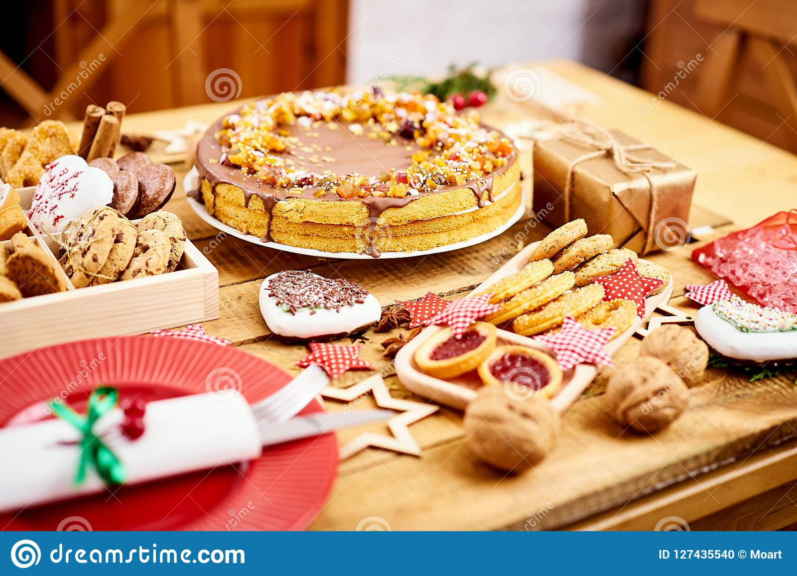 Wooden Table With Delicious Christmas Cake Decorations And Different