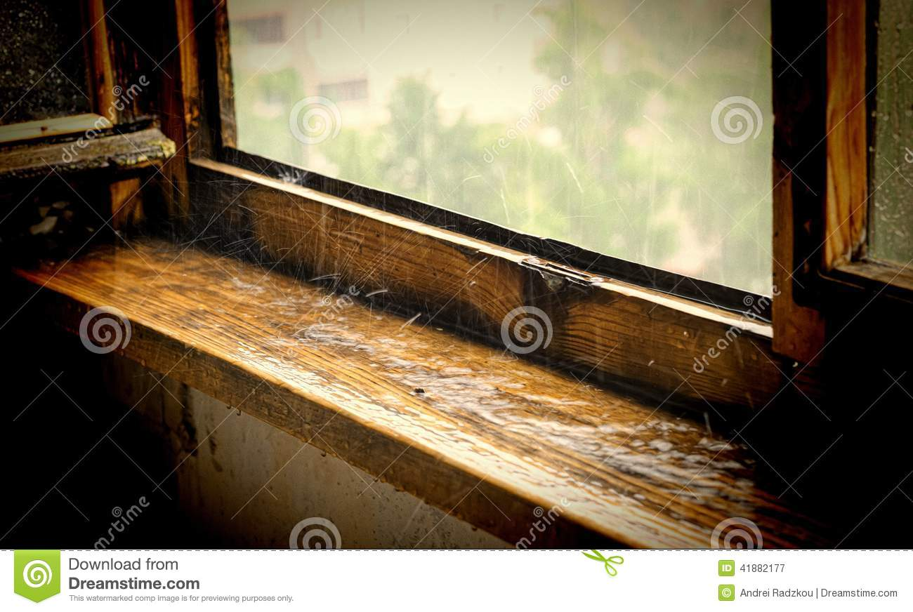 sill under a pouring rain raindrops breaking on old wooden window sill