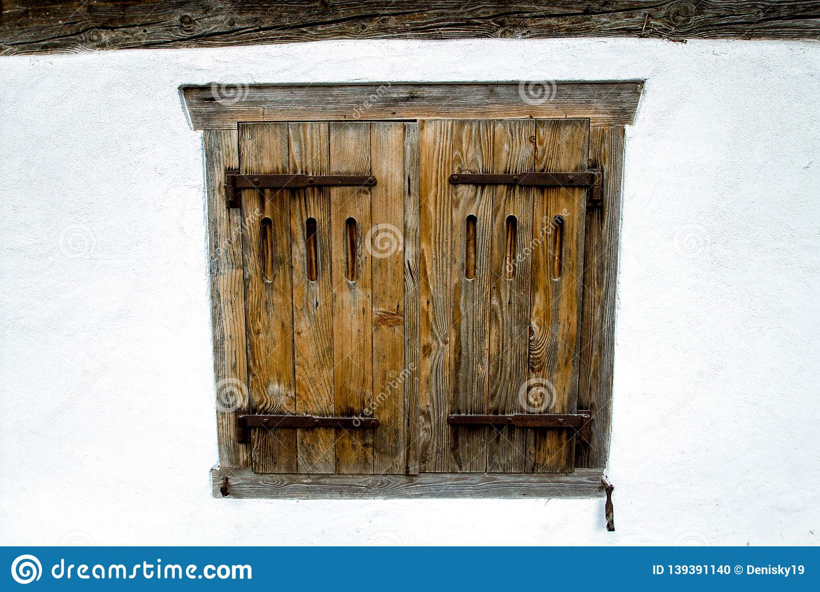 Old wooden window in a white wall. Building of Switzerland.