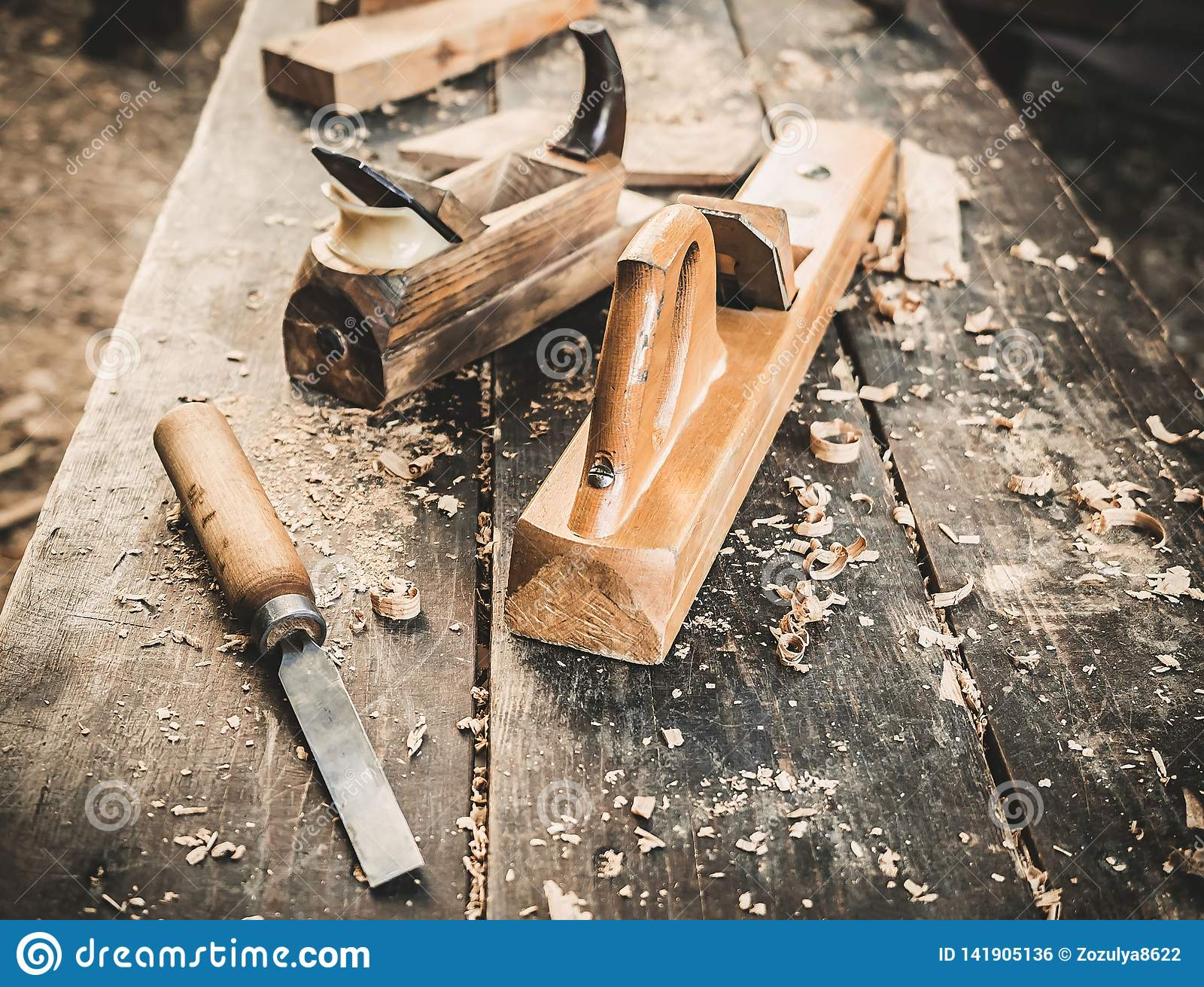 Old woodworking hand tool: wooden plane, chisel and drawing knife in a carpentry workshop on dirty rustic table covered
