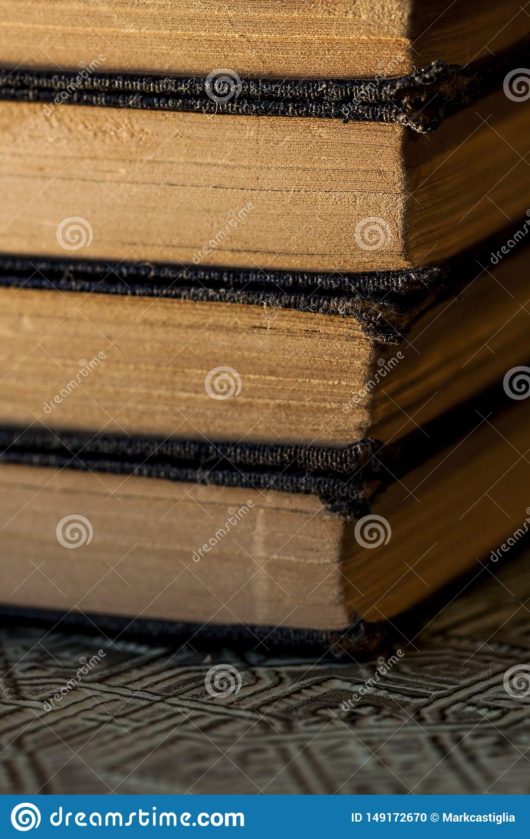 Old worn books stacked on textured surface close up