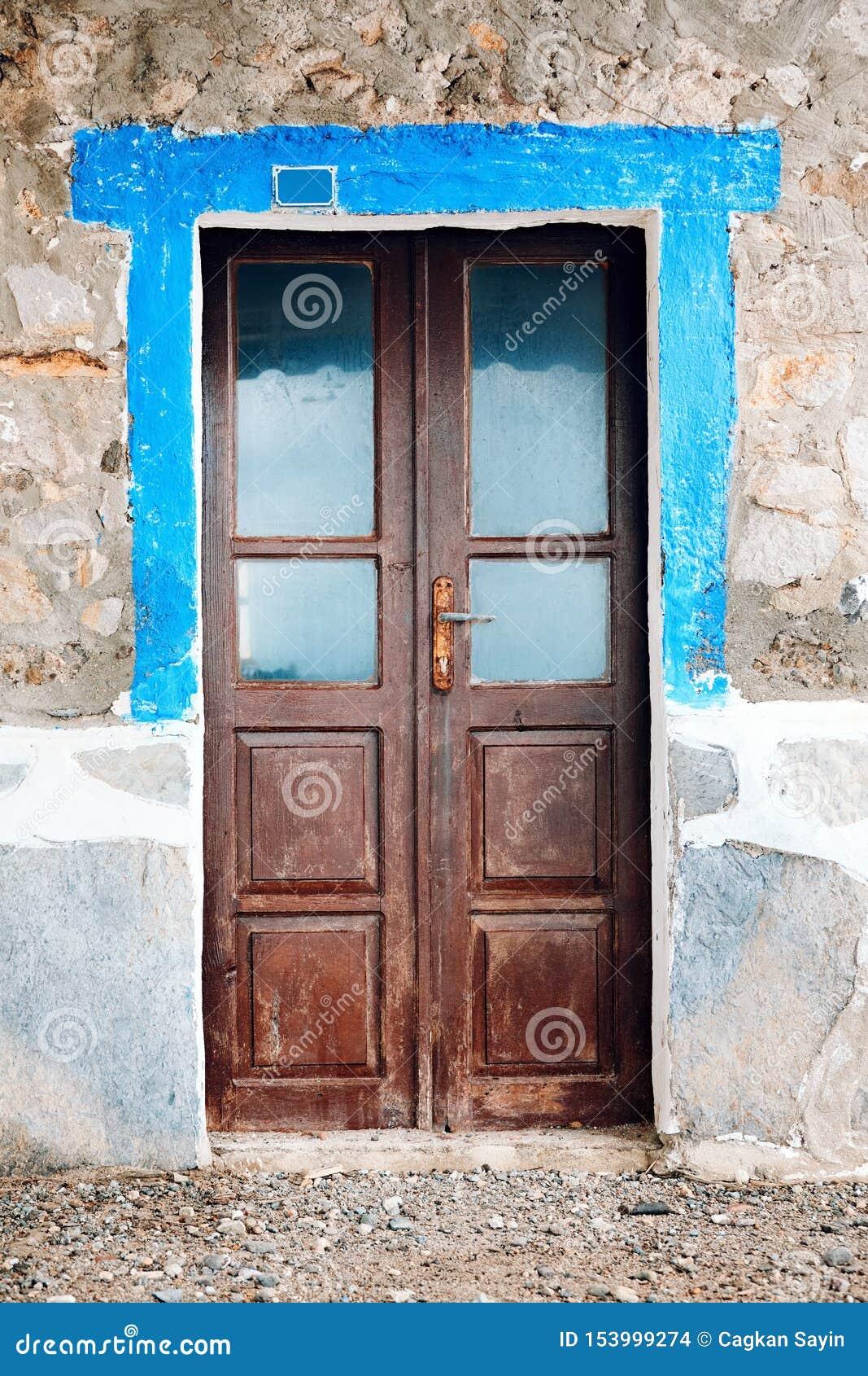Old worn brown wooden windowed door of a vintage stone house
