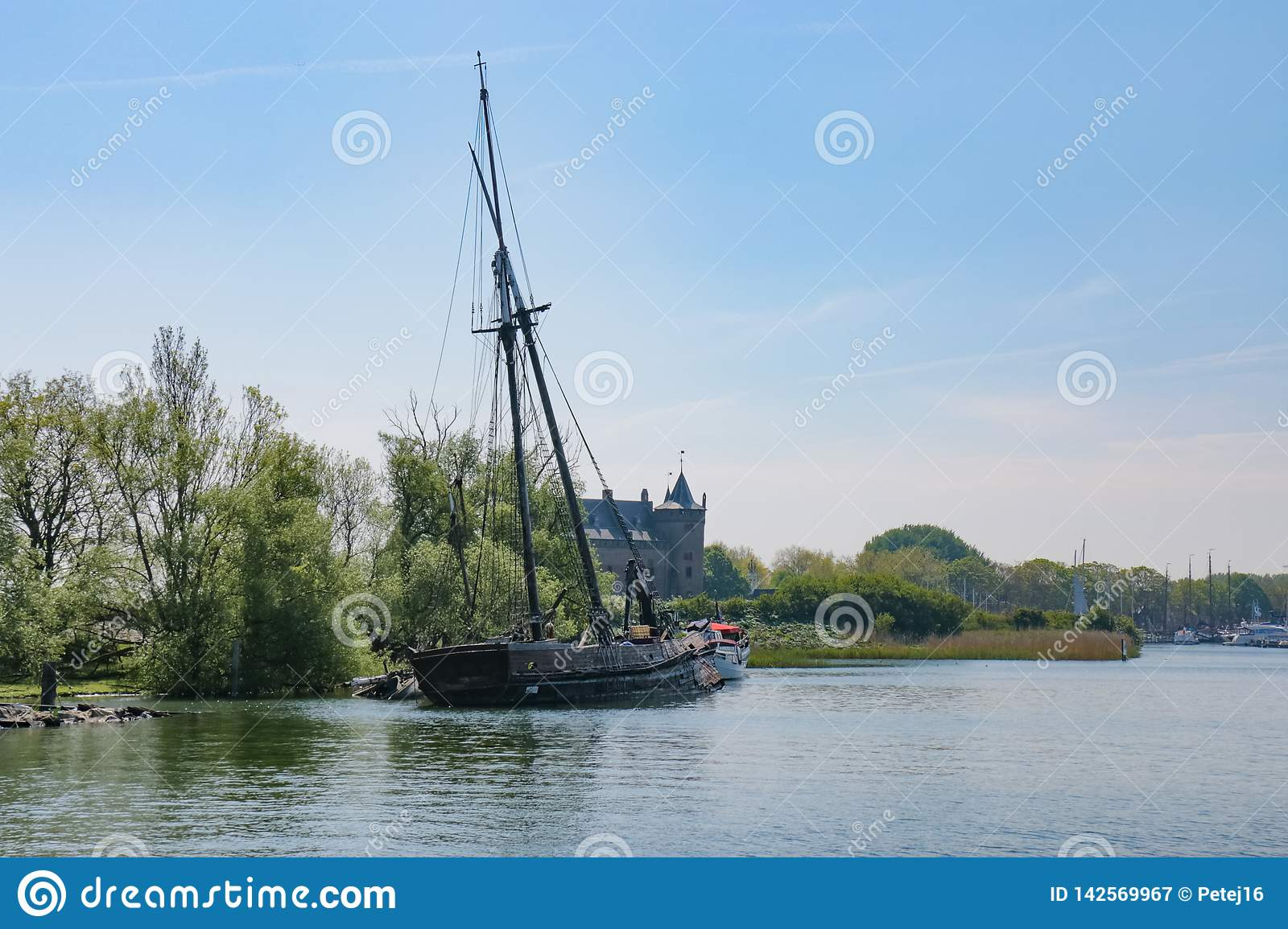 Old wrecked sailing ship on side of river canal