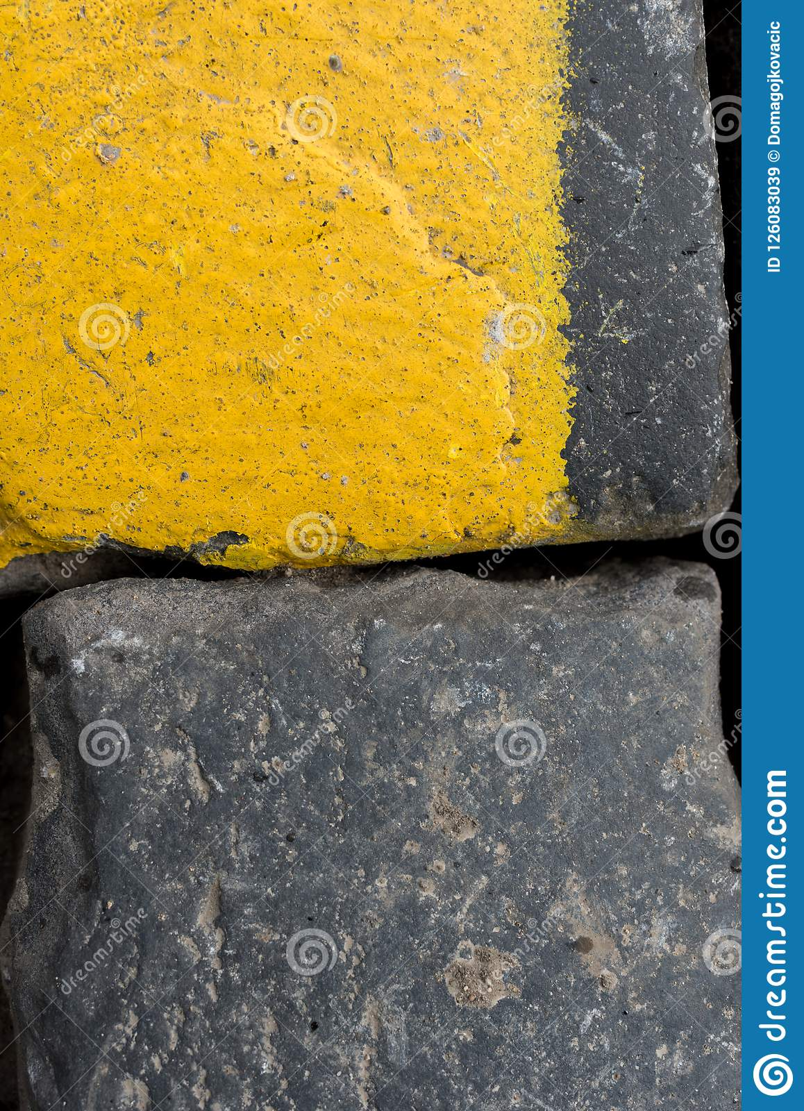Old yellow and black granite road cubes or cobbles as background or wallpaper. Vertical image.