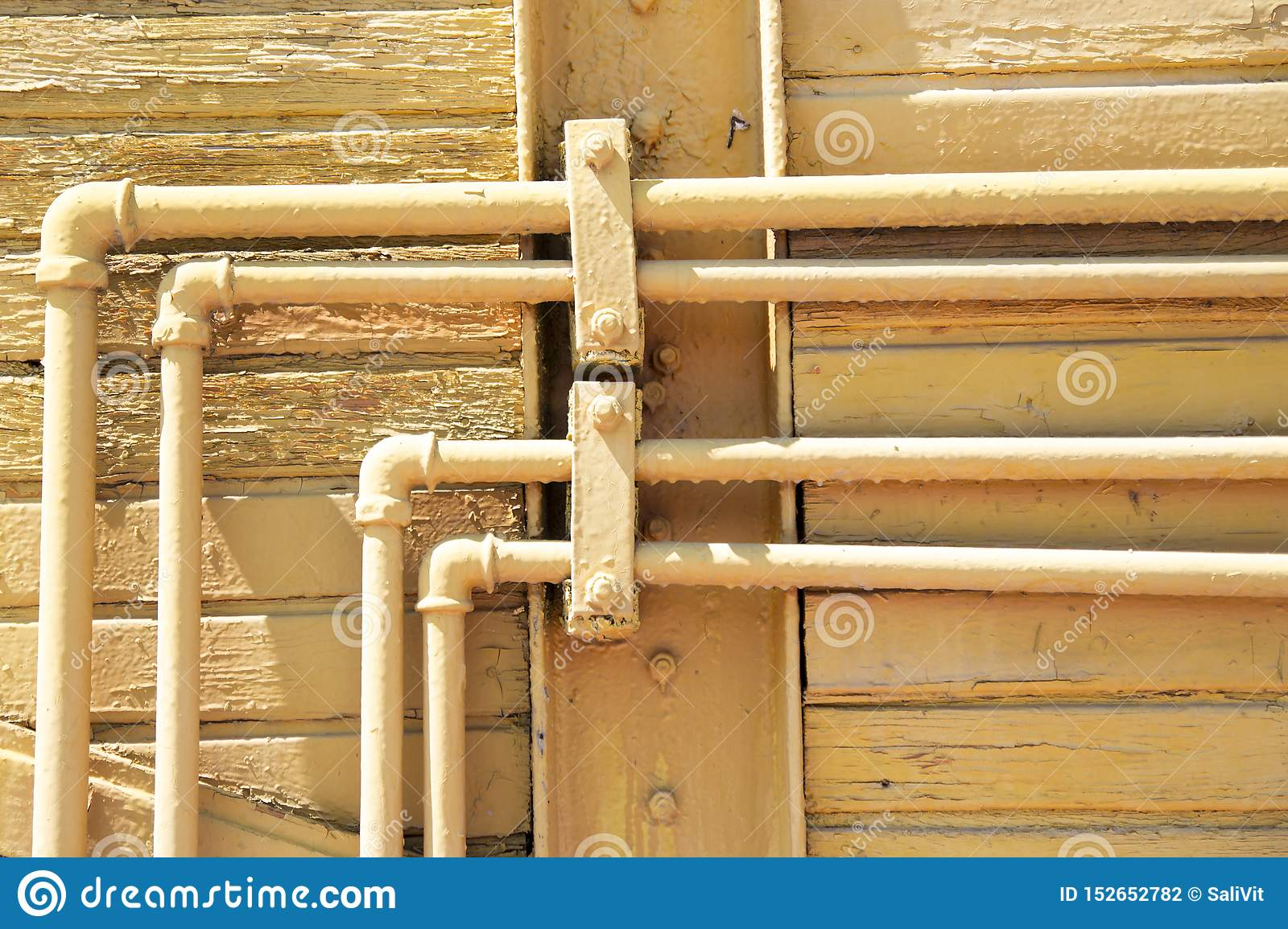 Old yellow pipes on the wooden wall. Scratch Grunge Urban country Background. Texture for your design.