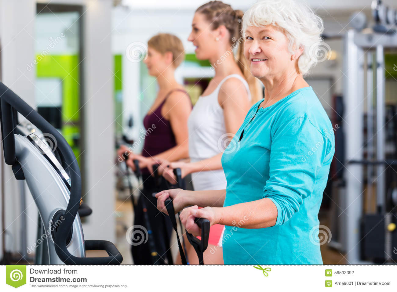 Old and young people on vibrating plates in gym