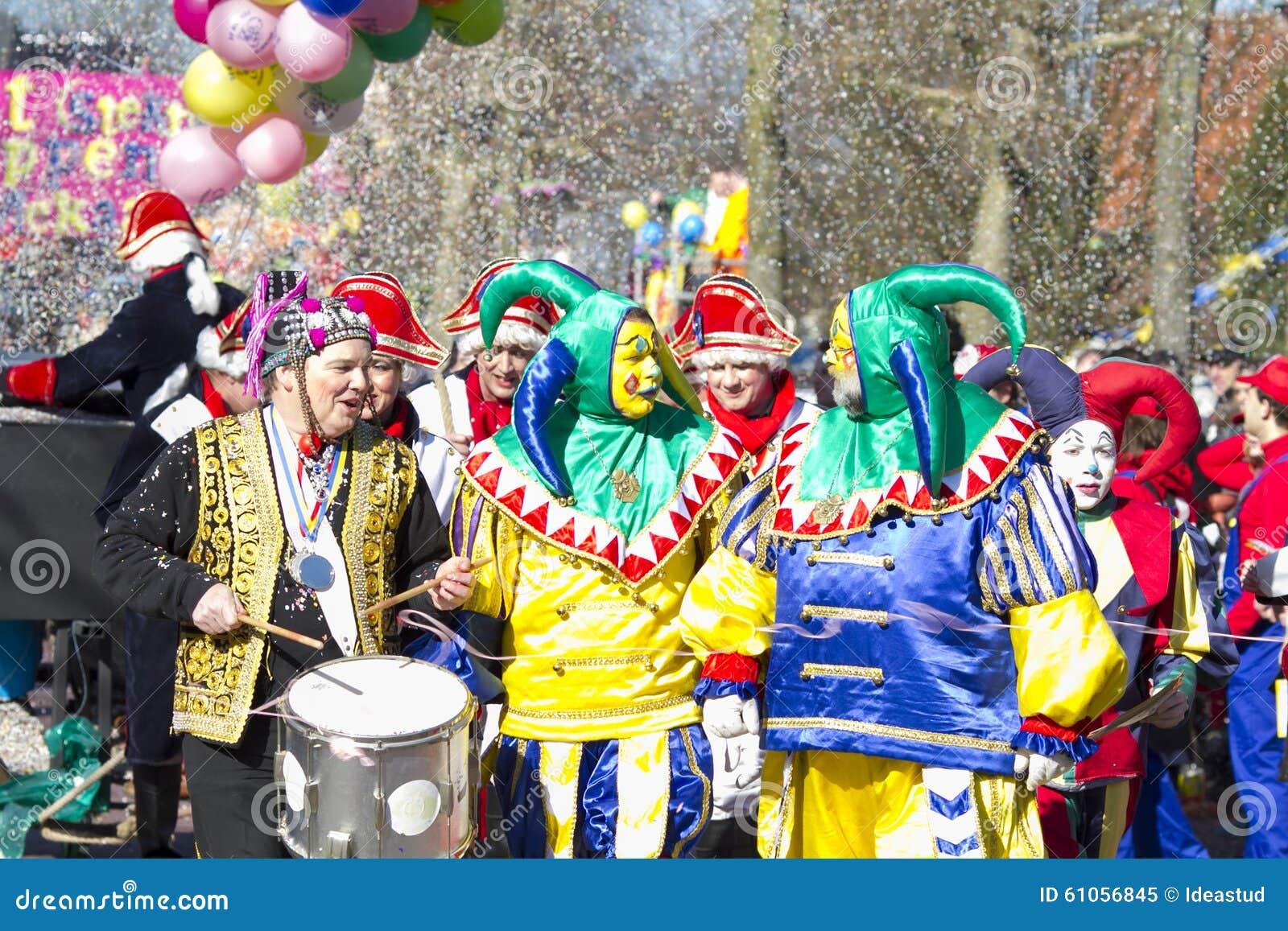 OLDENZAAL NEDERLÄNDERNA - MARS 6, 2011: Folket i färgglad karnevalklänning under den årliga karnevalet ståtar i Oldenzaal som är
