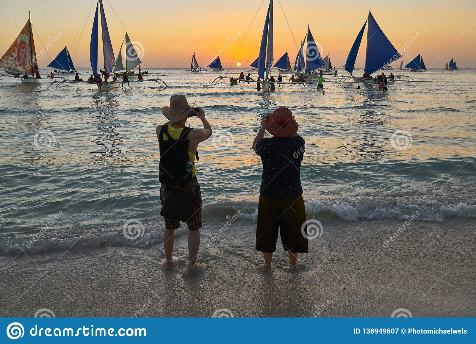 Older Asian couple enjoying taking pictures at sunset on Boracay