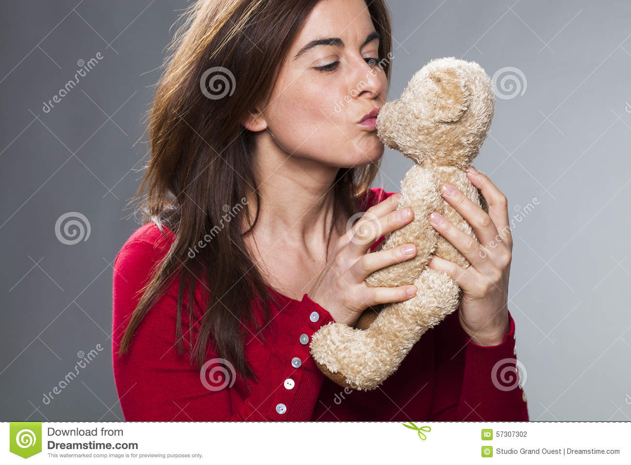 older attractive lady blowing her cuddly toy a kiss stock photo