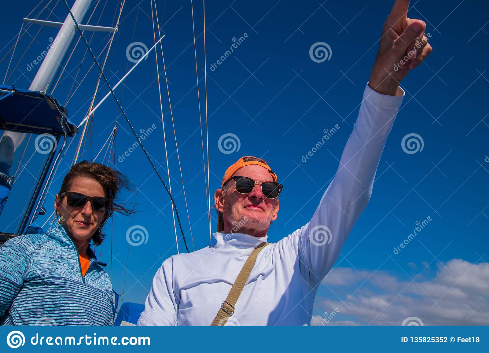 Older baby boomer caucasian couple with man pointing into the distance. Deep blue sky with sailboat rigging in background