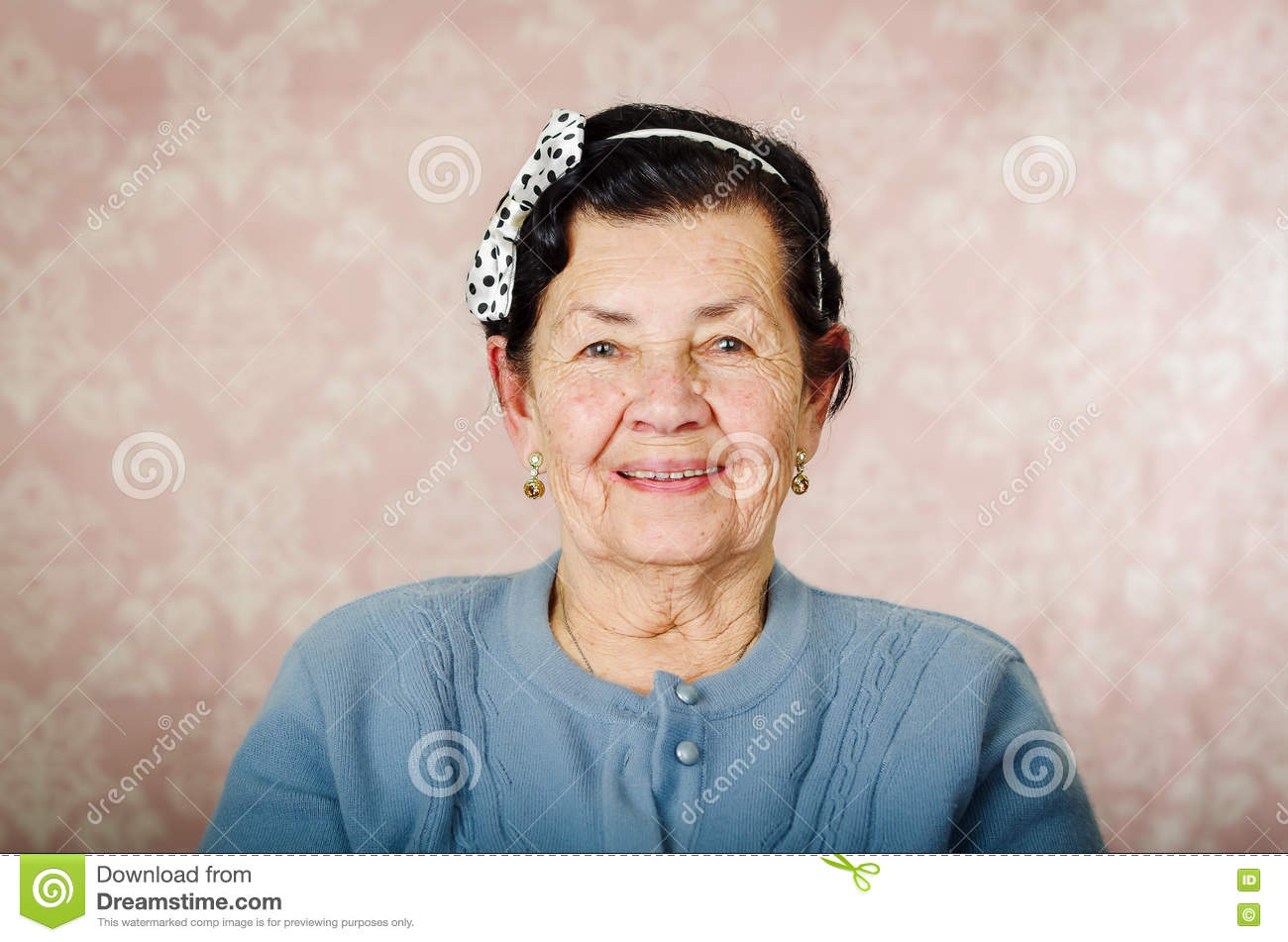 Older cute hispanic woman wearing blue sweater and polka dot bowtie on head smiling happily in front of pink wallpaper