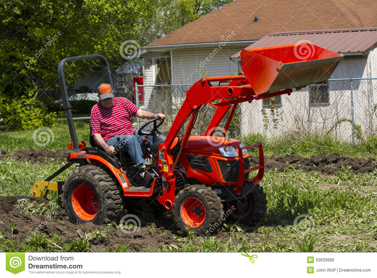 Older Farmer Plowing His Garden With A Compact Tractor