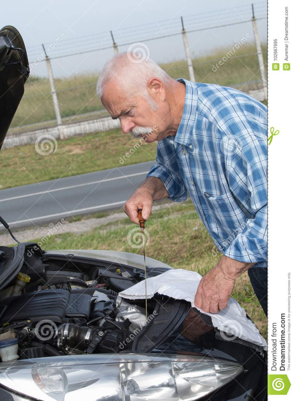Older man checking levels and servicing car