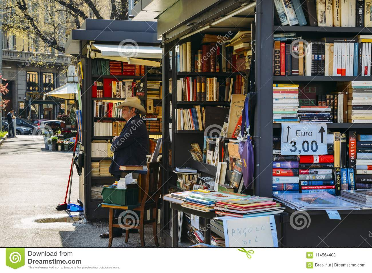 An older man with a cowboy hat sells books on the street