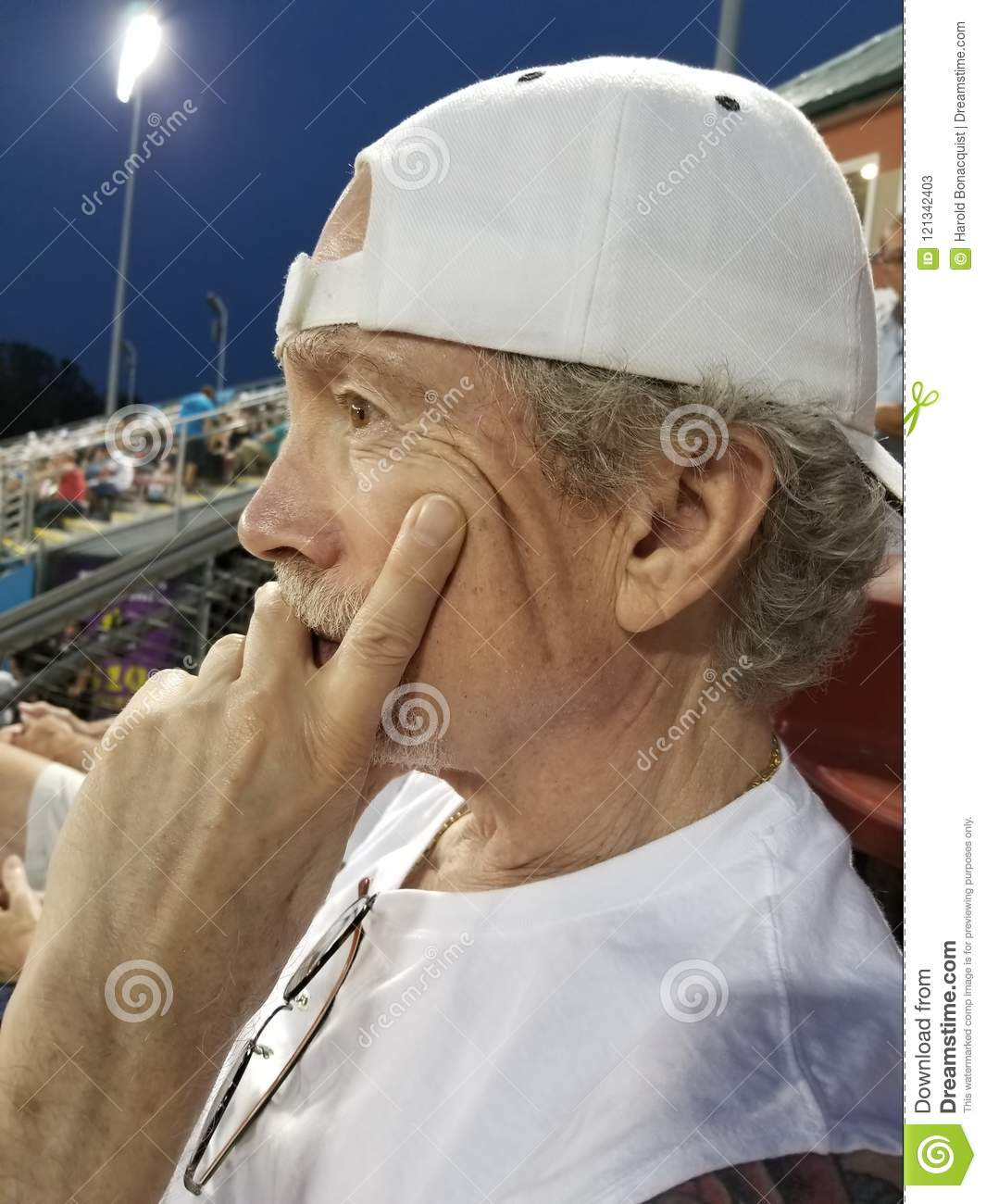 Older man with goatee and intent expression wearing white back b