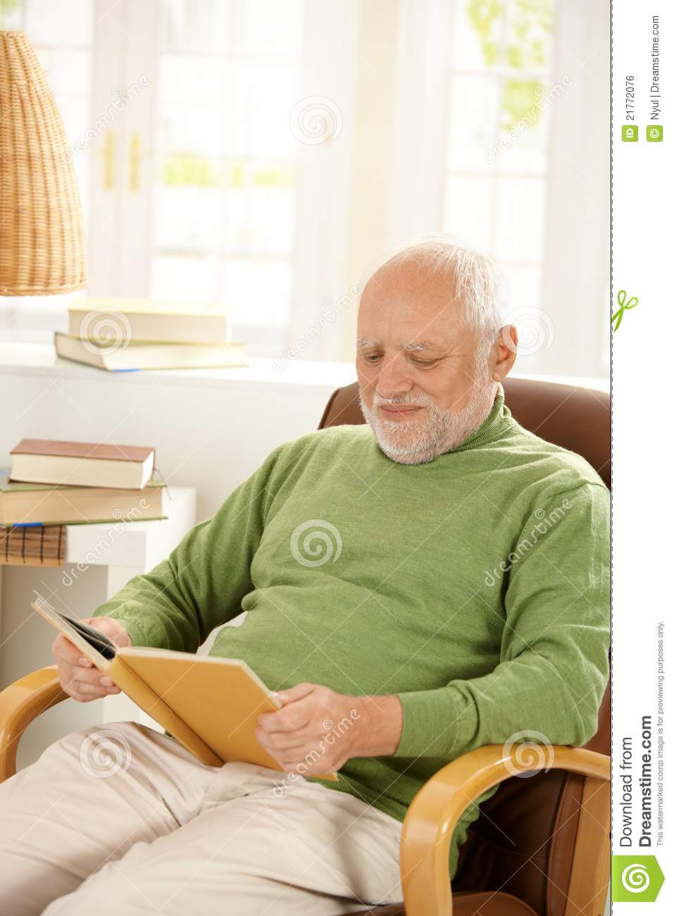 Older Man Relaxing At Home Reading Book Royalty Free