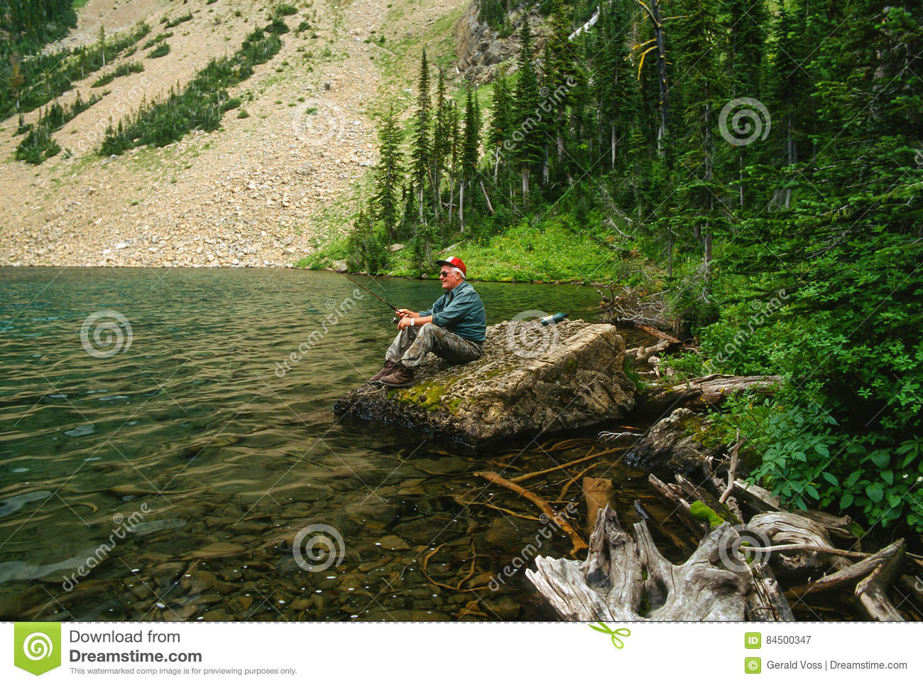 Older man sitting on a rock fishing a high mountain lake for Green mountain reservoir fishing