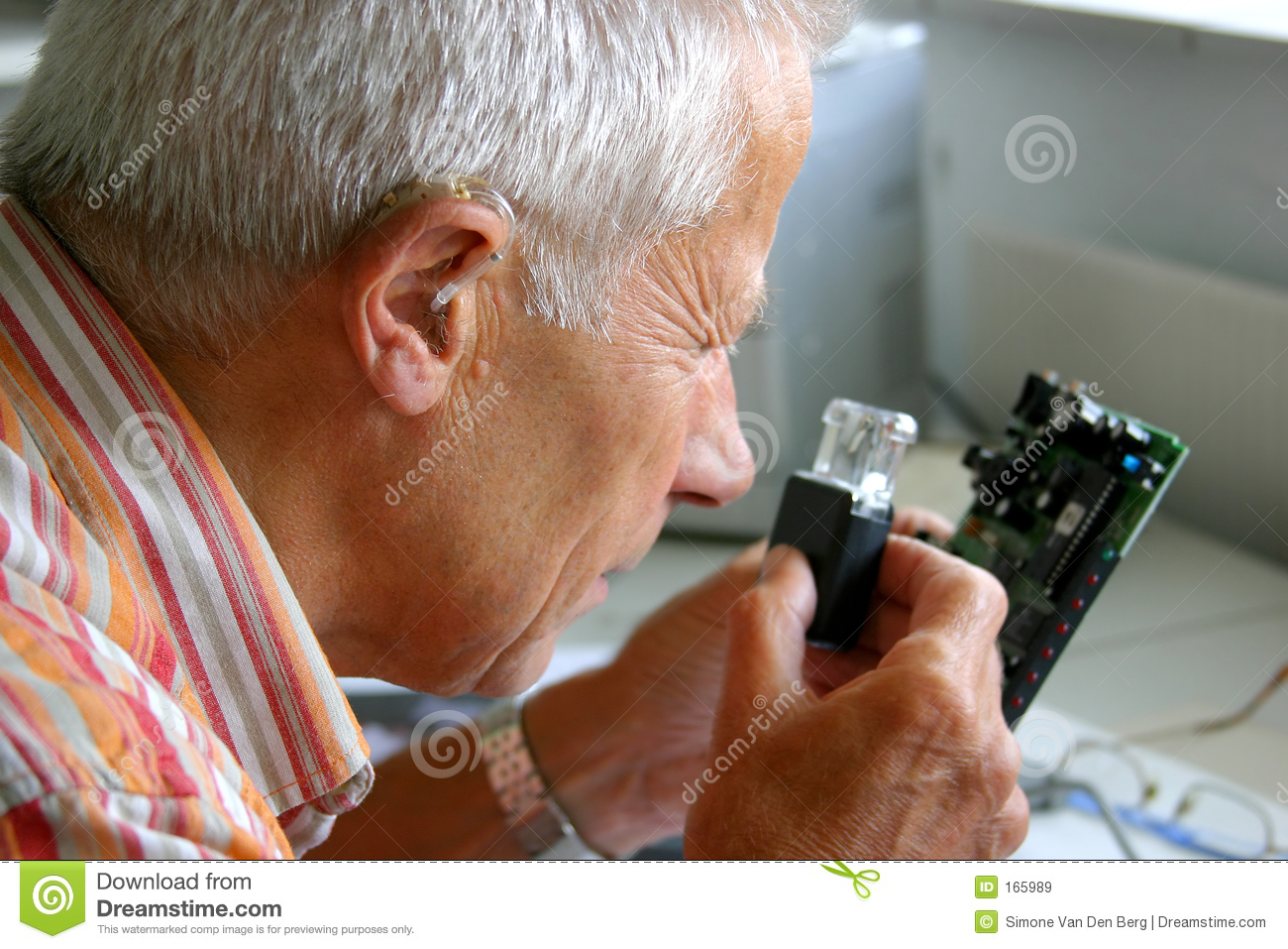 Older man trying to read the tiny letters on printboard