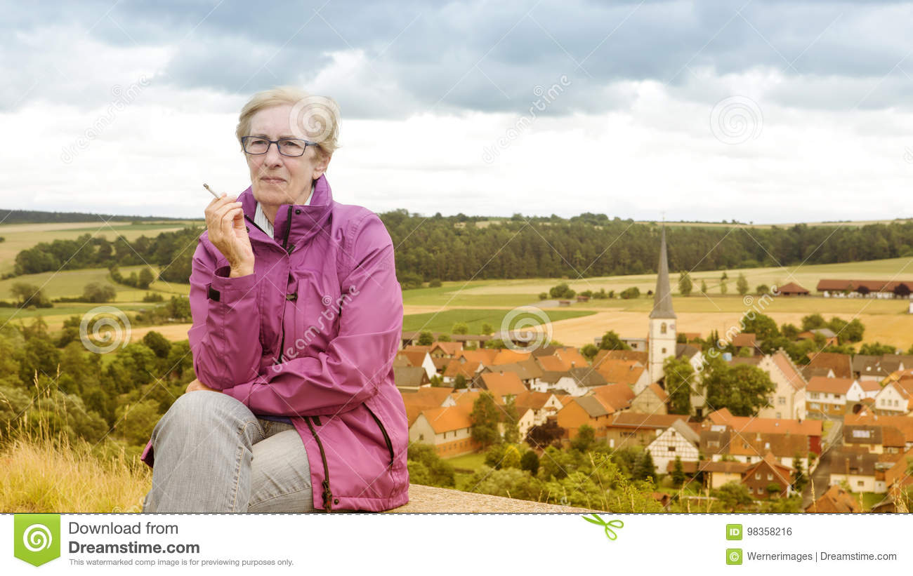 Older woman sitting on bench and smoking
