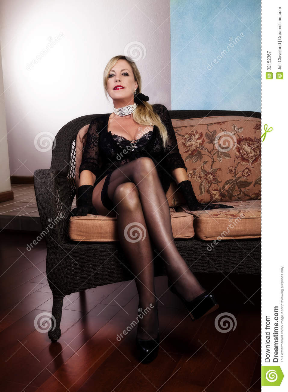 older woman sitting in black lingerie and stockings stock image