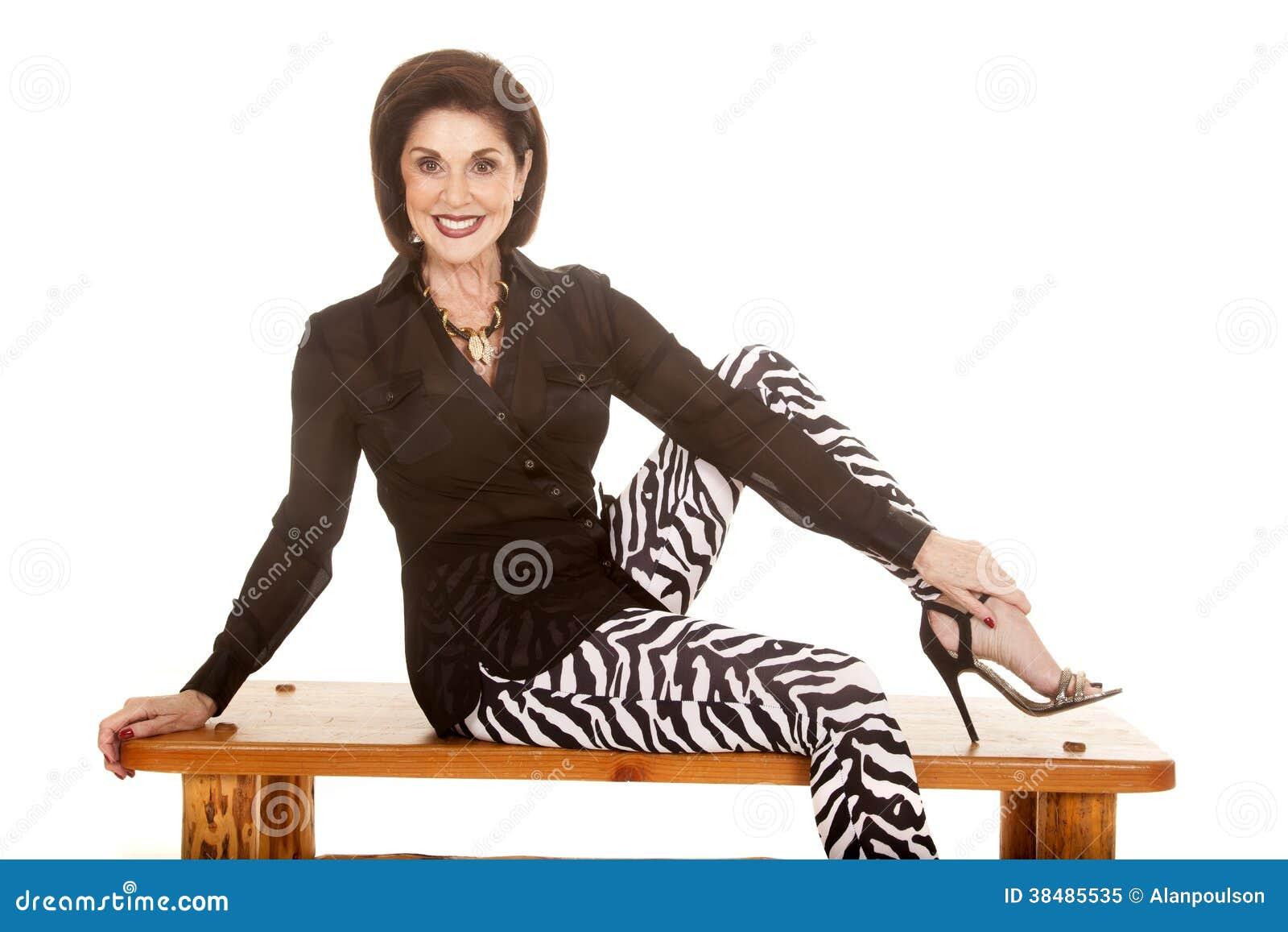 older woman zebra pants sit on bench smiling stock image